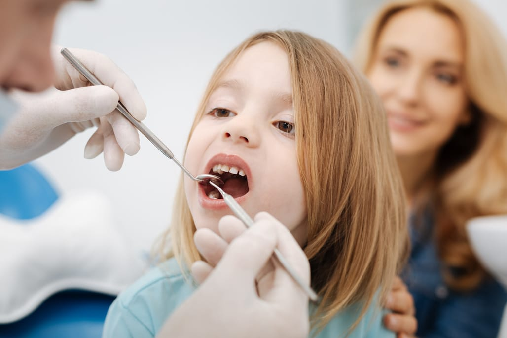 Gentle pediatric dentist doing a checkup