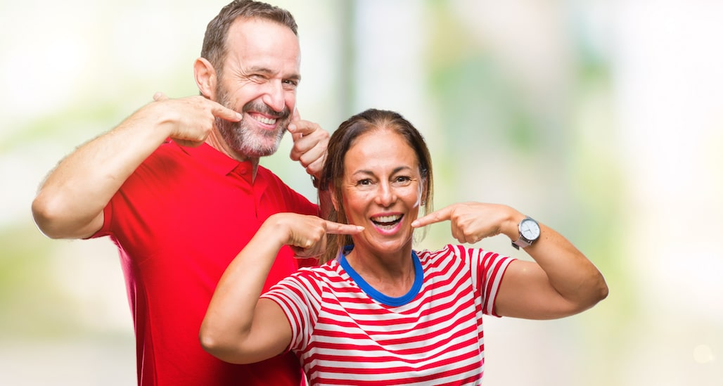 Middle age hispanic couple in love over isolated background smiling confident showing and pointing with fingers teeth and mouth. Health concept.
