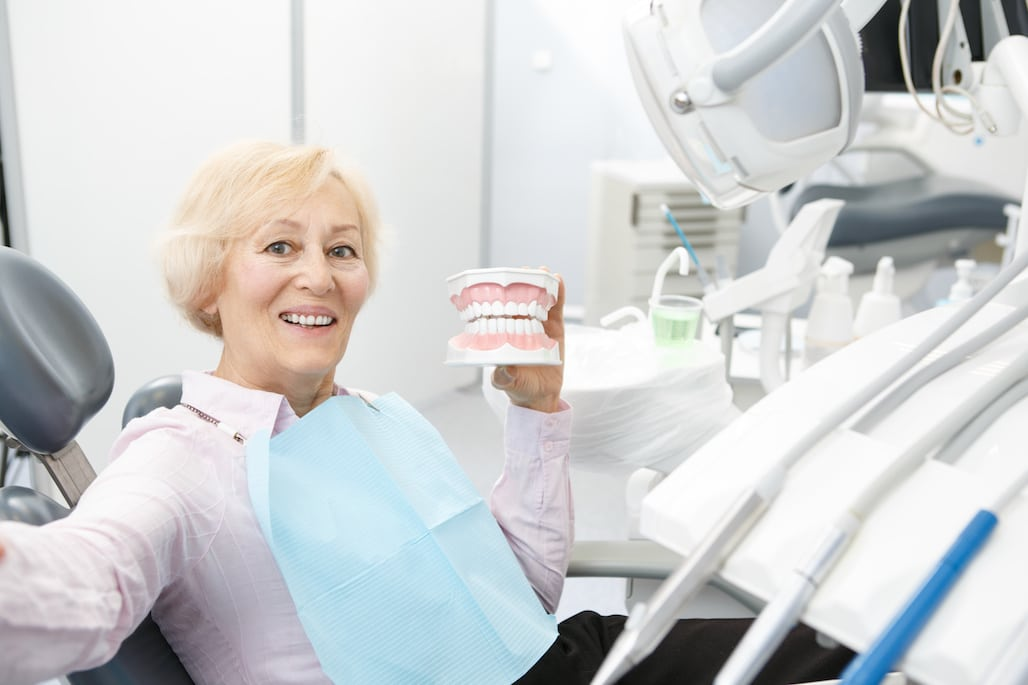 Senior woman making a selfie holding dental mold